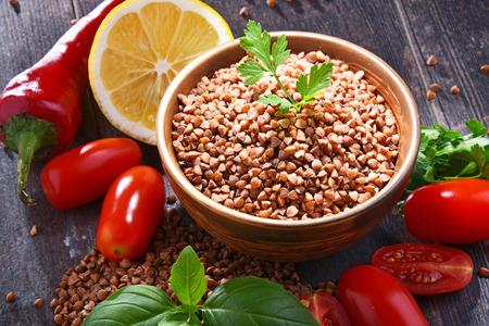 Bowl of buckwheat kasha on wooden table.