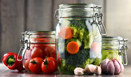 Jars with marinated food and organic raw vegetables. Banque d'images