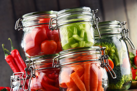 Jars with marinated food and organic raw vegetables. Imagens