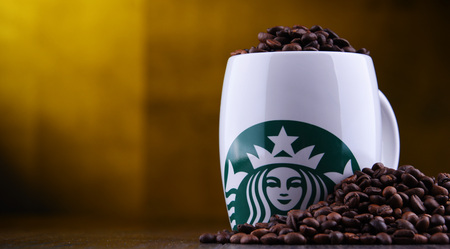 POZNAN, POL - DEC 30, 2018: Cup of Starbucks, the name of coffee company and coffeehouse chain, founded in Seattle, Wa. USA, in 1971; now the largest business of this kind in the world.