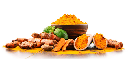 Bowl of turmeric powder over white background.