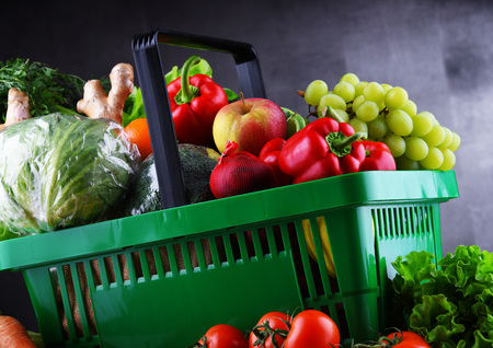 Fresh organic fruits and vegetables in plastic shopping basket.