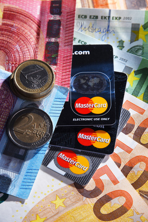 POZNAN, POL - APR 11, 2019: Euro currency and credit card of Mastercard, an American multinational financial services corporation headquartered in Purchase, New York, USA
