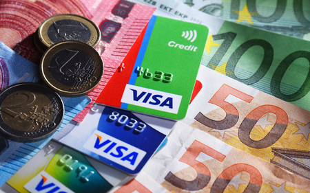POZNAN, POL - APR 11, 2019: Euro currency and credit card of Visa, a multinational financial services corporation headquartered in Foster City, California, USA Editorial
