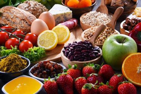 Composition avec un assortiment de produits alimentaires biologiques sur une table de cuisine en bois. Banque d'images
