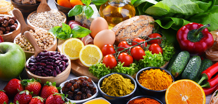 Composition avec un assortiment de produits alimentaires biologiques sur une table de cuisine en bois.