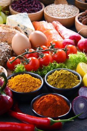 Composizione con prodotti alimentari biologici assortiti sul tavolo da cucina in legno.
