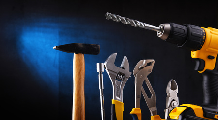 Composition with different kinds of hardware tools including cordless drill, monkey spanner, hammer and screwdriver