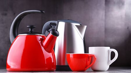 Traditional stovetop kettle with whistle and modern electric cordless kettle