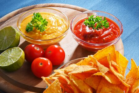 Composition with glass bowl of tortilla chips and dipping sauces.