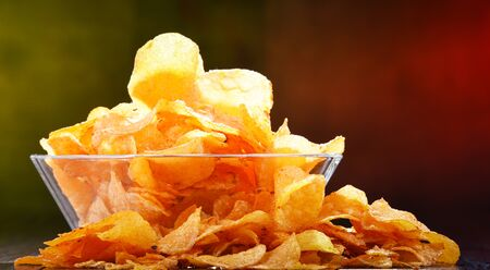 Composition with glass bowl of potato chips. Stock Photo
