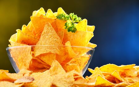 Composition with glass bowl of tortilla chips.
