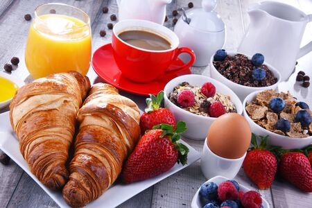 Breakfast served with coffee, orange juice, croissants, egg, cereals and fruits. Balanced diet.