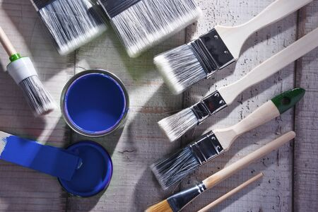 Paint can and paintbrushes of different size  for home decorating purposes.