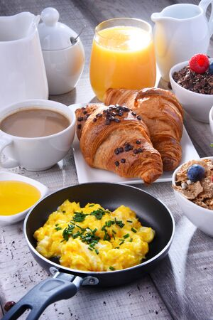 Breakfast served with coffee, orange juice, croissants, egg, cereals and fruits. Balanced diet. Stock Photo - 127118050