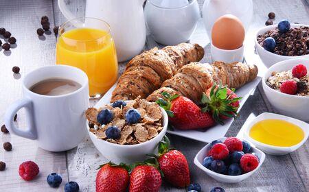 Śniadanie serwowane z kawą, sokiem pomarańczowym, rogalikami, jajkiem, płatkami zbożowymi i owocami. Zbilansowana dieta.