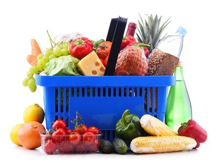 Cesta de la compra de plástico con una variedad de productos comestibles aislado en blanco