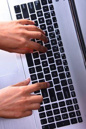 Hands typing on a laptop computer keyboard. 版權商用圖片