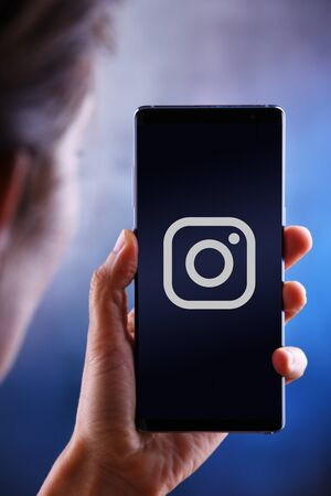POZNAN, POL - JUL 10, 2019: Woman holding smartphone displaying logo of Instagram, a photo and video-sharing social networking service owned by Facebook Editorial
