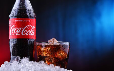 POZNAN, POL - AUG 13, 2019: A bottle and a glass of Coca-Cola, a carbonated soft drink manufactured by The Coca-Cola Company headquartered in Atlanta, Georgia, USA Editorial