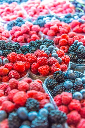 Raspberries, blueberries and blackbarries sold on the street market stall.