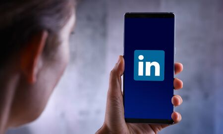 POZNAN, POL - JUL 10, 2019: Woman holding smartphone displaying logo of LinkedIn, an American business and employment-oriented service that operates via websites and mobile apps