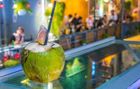 Fresh coconut drink served in the bar on the famous Train Street, popular tourist destination in old town Hanoi by night Stock Photo