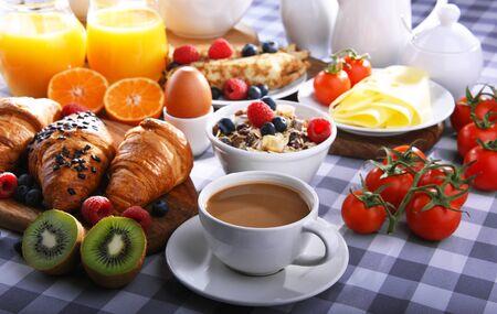 Śniadanie serwowane z kawą, sokiem pomarańczowym, rogalikami, naleśnikami, jajkiem, płatkami zbożowymi i owocami. Zdjęcie Seryjne