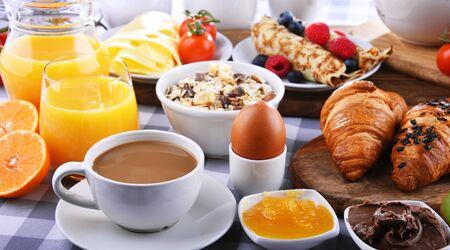 Frühstück mit Kaffee, Orangensaft, Croissants, Pfannkuchen, Ei, Müsli und Obst.