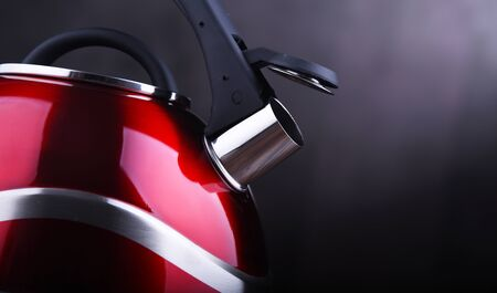 Composition with red stainless steel stovetop kettle with whistle