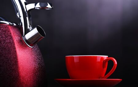 Red stainless steel stovetop kettle with whistle and cup of coffee Stockfoto