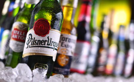 POZNAN, POL - DEC 23, 2019: Bottles of famous global beer brands including Heineken, Becks, Bud, Miller, Corona, Stella Artois, and Pilsner Urquell