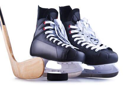 Par de patines de hockey sobre hielo con un palo y un disco aislado sobre fondo blanco. Foto de archivo