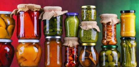 Jars with variety of pickled vegetables and fruits. Preserved food