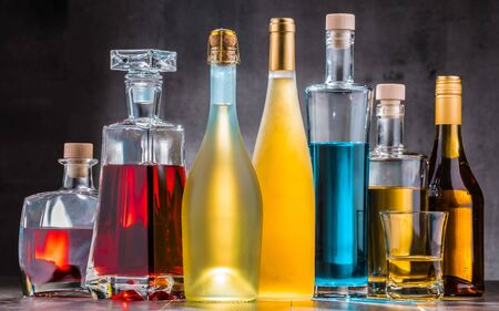 Composition with carafe and bottles of assorted alcoholic beverages.