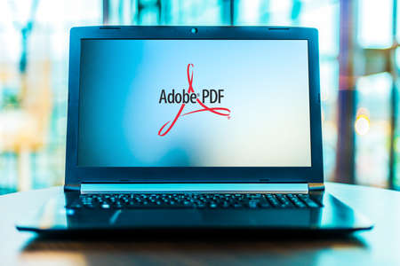 POZNAN, POL - MAR 24, 2020: Laptop computer displaying logo of Adobe Acrobat, a family of application software and Web services developed by Adobe Inc.