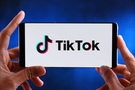 POZNAN, POL - FEB 19, 2020:  Hands holding smartphone displaying logo of TikTok, a Chinese video-sharing social networking service owned by ByteDance