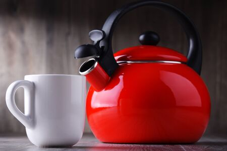 Cup of coffee and stainless steel stovetop kettle with whistle.