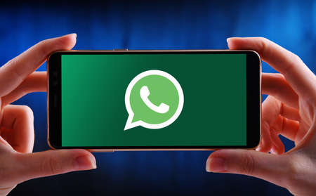 POZNAN, POL - MAY 21, 2020: Hands holding smartphone displaying logo of WhatsApp Messenger, a freeware, cross-platform messaging and Voice over IP (VoIP) service owned by Facebook