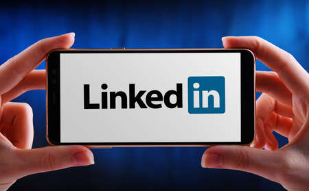 POZNAN, POL - MAY 21, 2020: Hands holding smartphone displaying logo of LinkedIn, an American business and employment-oriented service that operates via websites and mobile apps