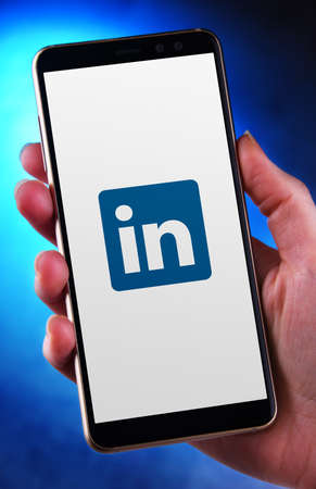 POZNAN, POL - MAY 21, 2020: Hand holding smartphone displaying logo of LinkedIn, an American business and employment-oriented service that operates via websites and mobile apps