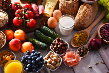 Composition with assorted organic food products on wooden kitchen table.