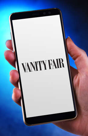 POZNAN, POL - JUN 12, 2020: Hand holding smartphone displaying logo of Vanity Fair, a monthly magazine of pop culture, fashion, and current affairs published by Cond