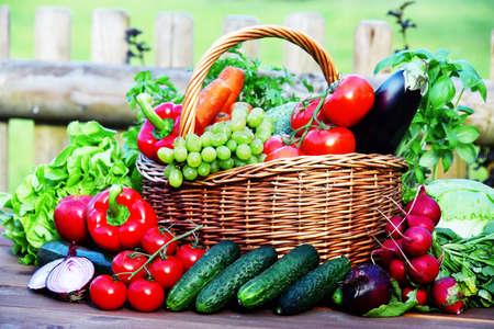 Variety of fresh organic vegetables in wicker basket. Banco de Imagens