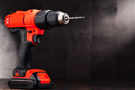 Cordless drill with drill bit working also as screw gun. 写真素材