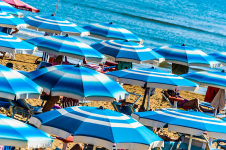 VIESTE, ITALY - SEP 8, 2020: Umbrellas on the sandy sea beach during hot summer day