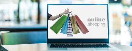 Paper shopping bags on laptop computer screen. Shopping online. E-commerce