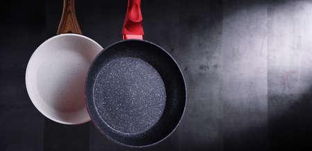 Two hanging stainless frying pans. Kitchen utensils Standard-Bild
