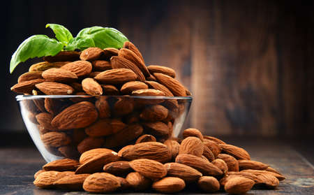 Bowl with shelled almonds on wooden table.