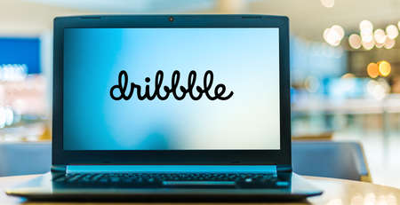 POZNAN, POL - JAN 6, 2021: Laptop computer displaying logo of Dribbble, a self-promotion and social networking platform for digital designers and creatives Editorial
